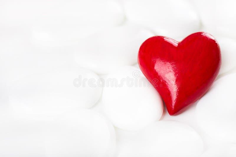 Il cuore ornamentale rosso su un fondo bianco con le pietre per accoglie immagine stock