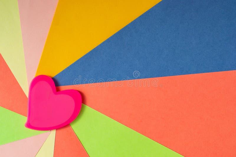 Il cuore rosa su carta colorata sotto forma di raggi parte dal bordo sinistro immagini stock libere da diritti