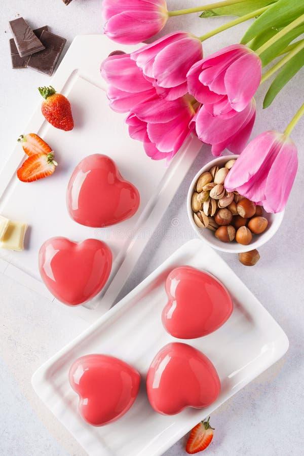 Il cuore rosso ha modellato i dolci della mousse con le bacche ed il cioccolato immagine stock