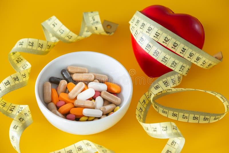 Il cuore si è avvolto con un metro d'adattamento e una ciotola di medicine immagini stock libere da diritti