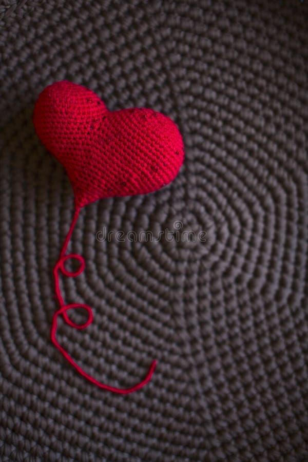 Il cuore tricottato rosso ha tricottato tricottare marrone del fondo del tessuto, fotografia stock