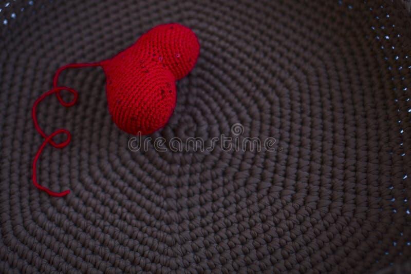 Il cuore tricottato rosso ha tricottato tricottare marrone del fondo del tessuto, fotografie stock