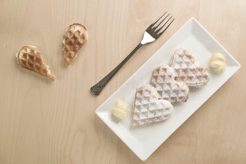 Il cuore waffles scorza di limone, lo zucchero in polvere servito sulla p rettangolare immagine stock