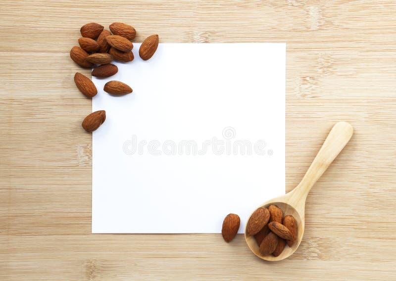 Il dado delle mandorle si è sbucciato con del cucchiaio della carta e derisione di legno di bianco su sopra fotografia stock libera da diritti