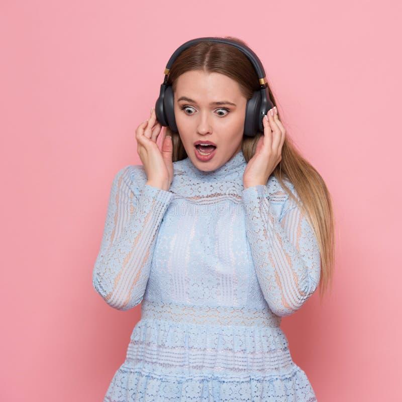 Il dancing emozionante della donna ed ascolta le cuffie d'uso di musica in parete rosa fotografia stock libera da diritti