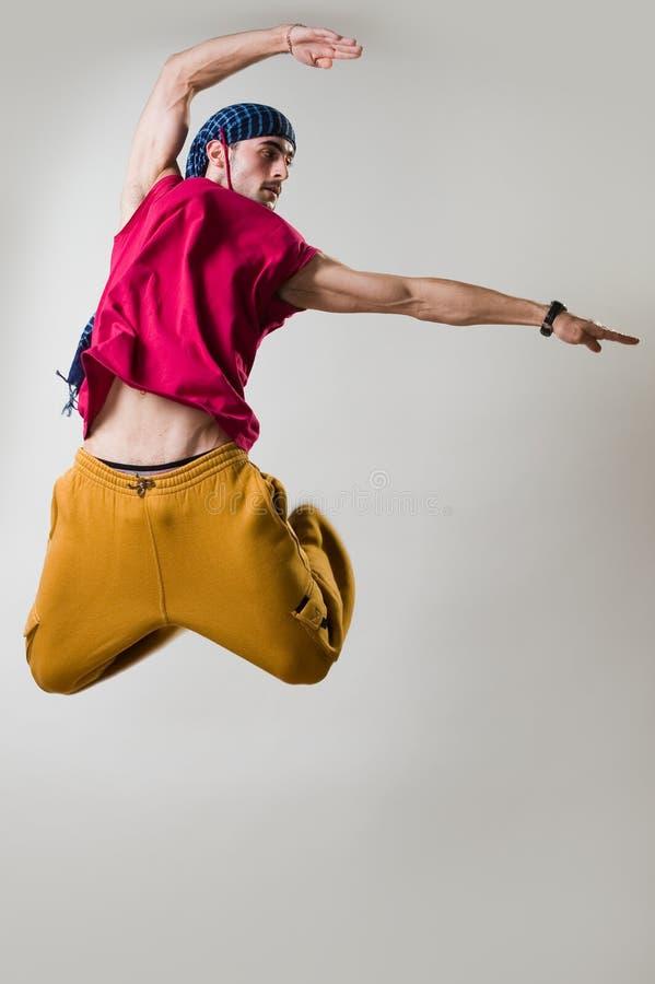 Il danzatore che salta sopra la priorità bassa chiara fotografie stock