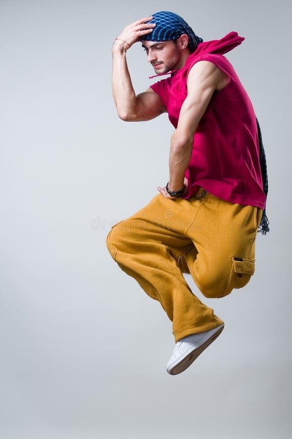 Il danzatore che salta sopra la priorità bassa grigia immagini stock libere da diritti