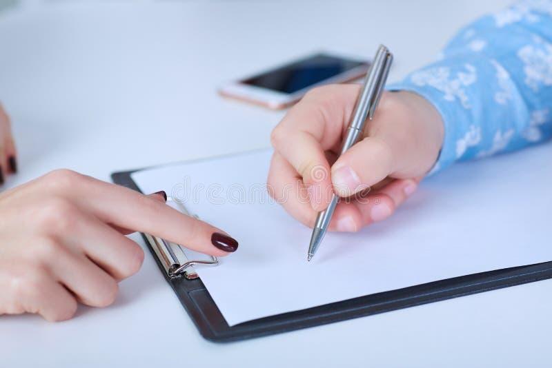 Il datore di lavoro forza l'impiegato redigere una lettera di dimissioni Consegna appena la tavola fotografia stock libera da diritti