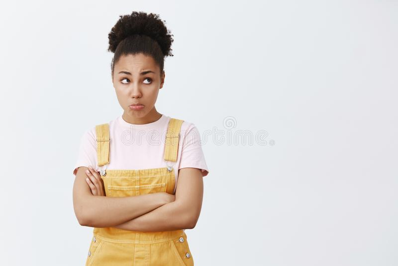 Il datore di lavoro ha gridato sul lavoratore part-time femminile dalla carnagione scura sveglio povero in camici gialli, in labb fotografie stock