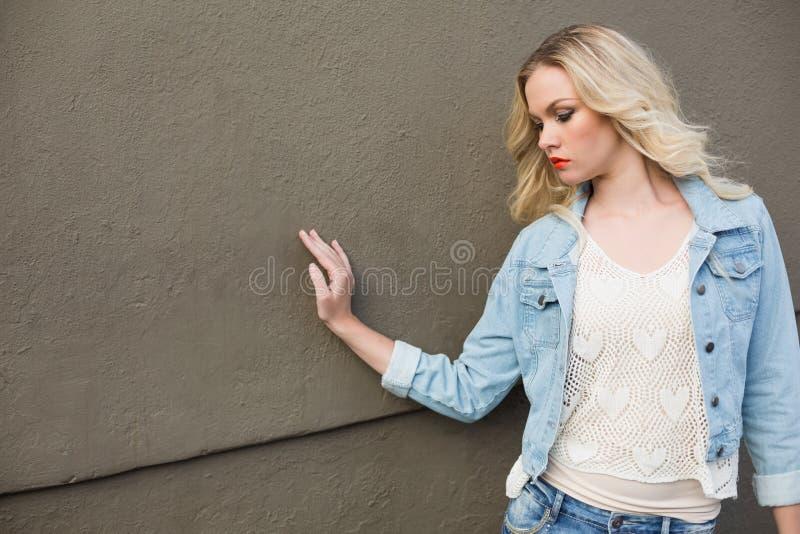 Il denim d'uso della bionda casuale splendida copre la posa all'aperto immagini stock libere da diritti
