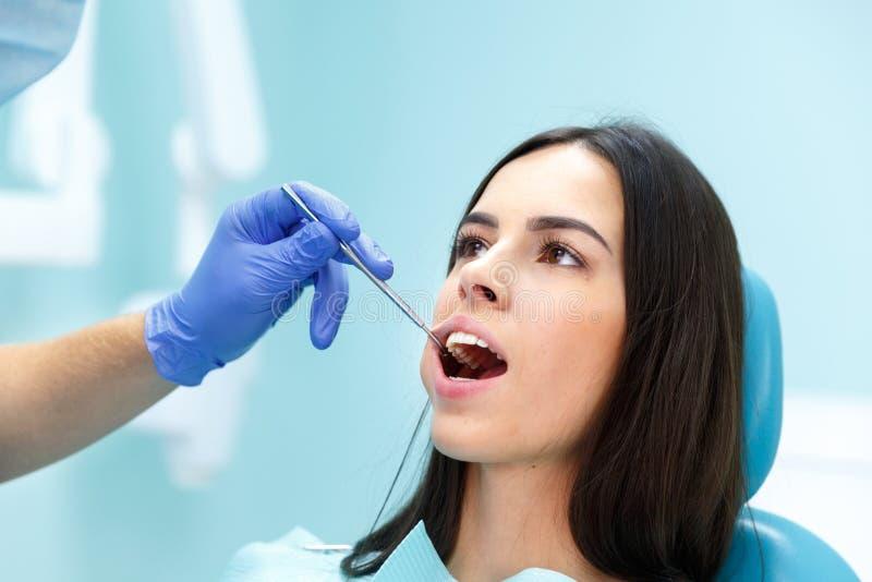 Il dentista esamina i denti di una ragazza alla sua ricezione fotografie stock