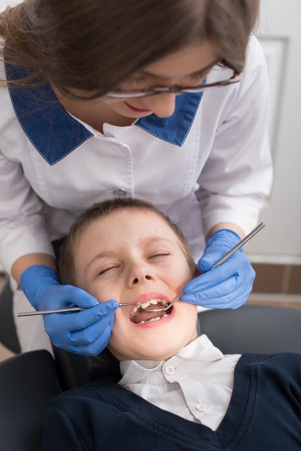 Il dentista femminile esamina i denti del bambino paziente immagine stock libera da diritti