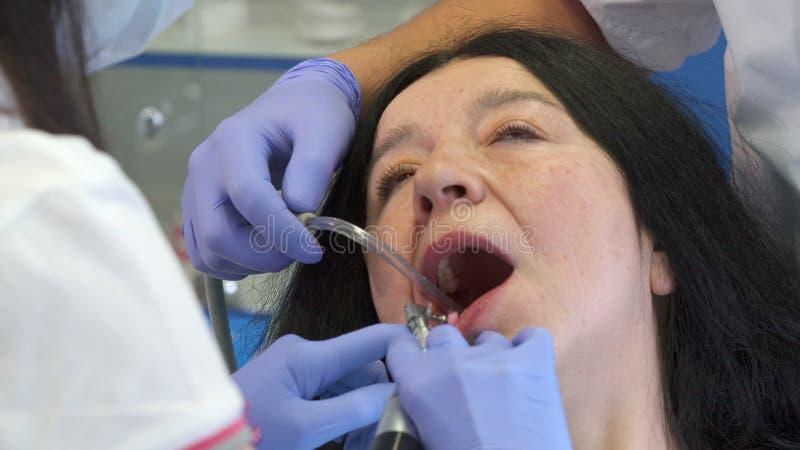 Il dentista lucida i denti più bassi del ` s del cliente fotografie stock libere da diritti