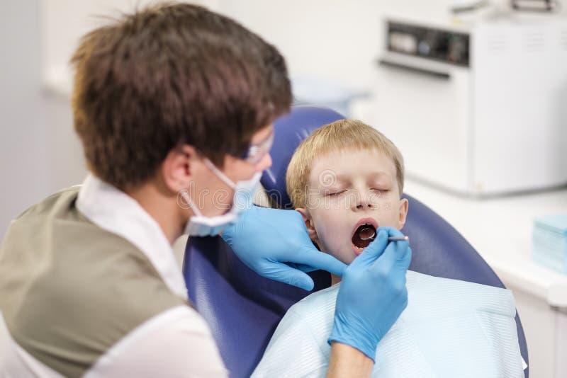 Il dentista maschio esamina i denti del ragazzo allegro paziente immagine stock