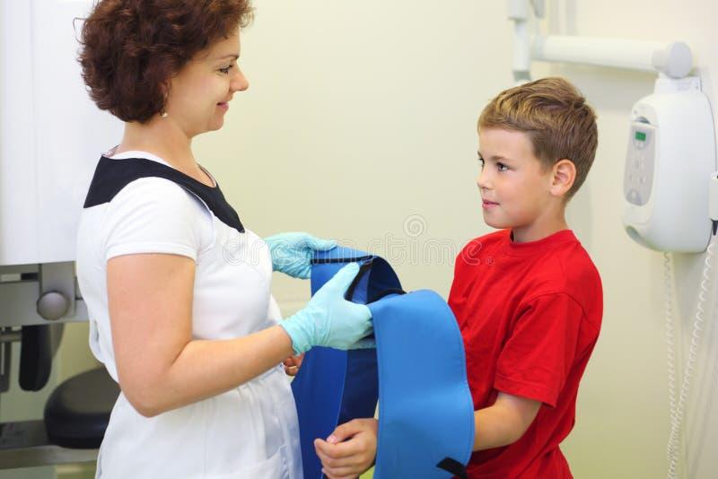 Il dentista porta il grembiule protettivo del cavo al ragazzo fotografia stock