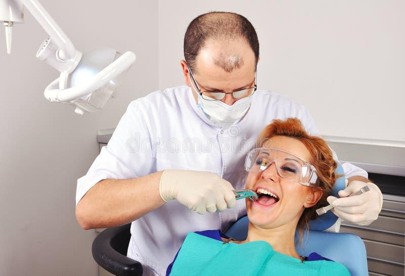 Il dentista rimuove il dente fotografia stock libera da diritti