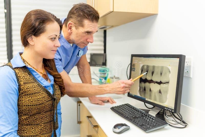 Il dentista spiega paziente sia esaminando i raggi x immagini stock