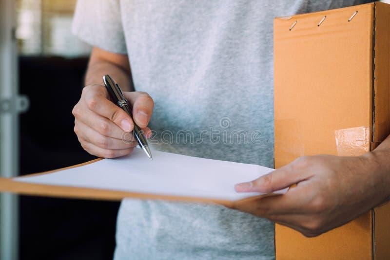Il destinatario alto vicino del prodotto sta usando la penna che firma per rilasciare una ricevuta il documento alla parte anteri fotografia stock libera da diritti