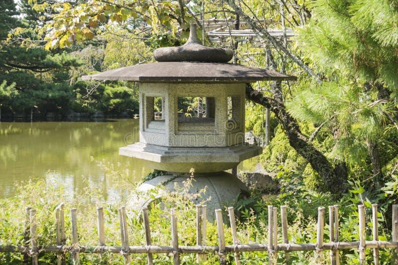 Il dettaglio del giardino orientale con la lanterna di pietra e lo stagno di Heian Jiungu shrine a Kyoto, Giappone immagine stock