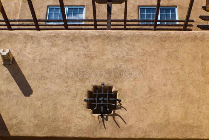 Il dettaglio della costruzione sudoccidentale rustica dello stucco con i vigas ed il ferro funzionano fotografia stock