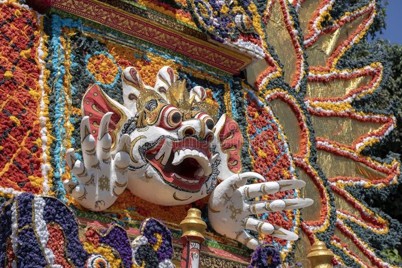 Il dettaglio ha offerto la torre di cremazione con le sculture tradizionali di balinese dei demoni e dei fiori sulla via centrale immagini stock