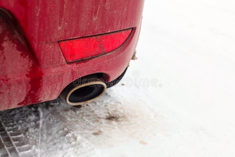 Il dettaglio sul tubo di scarico di un'automobile rossa ha parcheggiato su neve fotografia stock