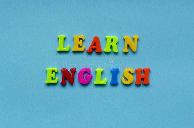 Il ` di frase impara il ` inglese delle lettere magnetiche di plastica colorate sul fondo della carta blu fotografia stock