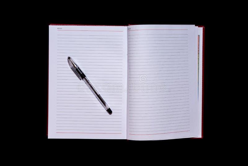 Il diario con le pagine in bianco nel centro del telaio e di una penna sulla cima, un fondo isolato nero, spase della copia, fals fotografia stock