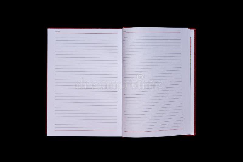 Il diario con le pagine in bianco nel centro del telaio, fondo isolato nero, spase della copia, falso su immagini stock