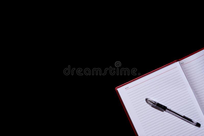 Il diario con le pagine in bianco nell'angolo del telaio e di una penna sulla cima, un fondo isolato nero, spase della copia immagine stock