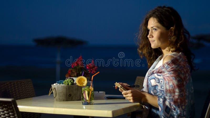 Il diario felice della tenuta della giovane donna con le memorie romantiche, si rilassa alla spiaggia immagini stock libere da diritti