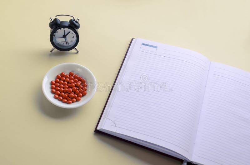Il diario, i farmaci e le ore, mangiano le pillole in tempo, scrivono nel calendario e nel diario Copi lo spazio immagini stock