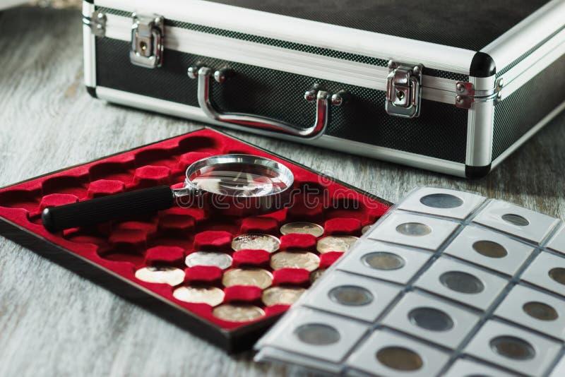 Il ` differente s del collettore conia nella scatola per le monete e una lente d'ingrandimento fotografia stock libera da diritti