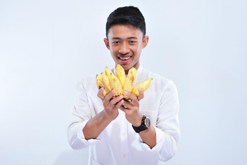 Il digiuno felice del giovane uomo musulmano quando rompe il Iftar veloce e il suhoor mangiano la banana gialla fotografia stock