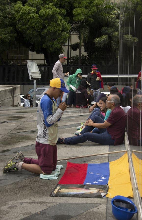 Il dimostrante dice che un pregare prima della partecipazione nel caso ha chiamato la madre di tutte le proteste nel Venezuela co fotografia stock