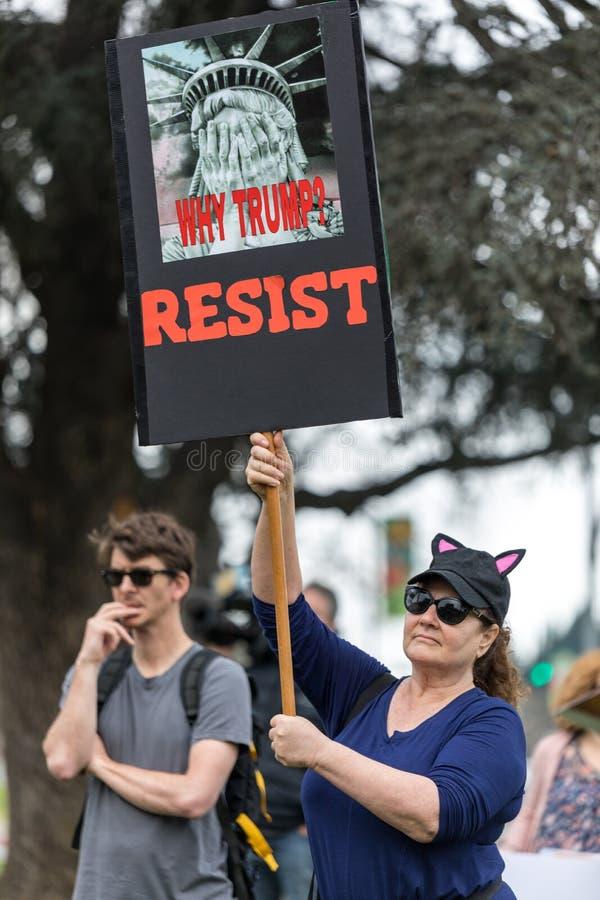 Il dimostrante tiene un segno che legge, ` perché Trump? RESISTA al ` fotografia stock libera da diritti