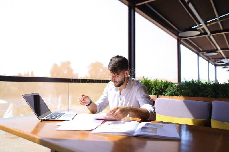 Il direttore di marketing lavora con i documenti ed il computer portatile di statistica alla t fotografie stock