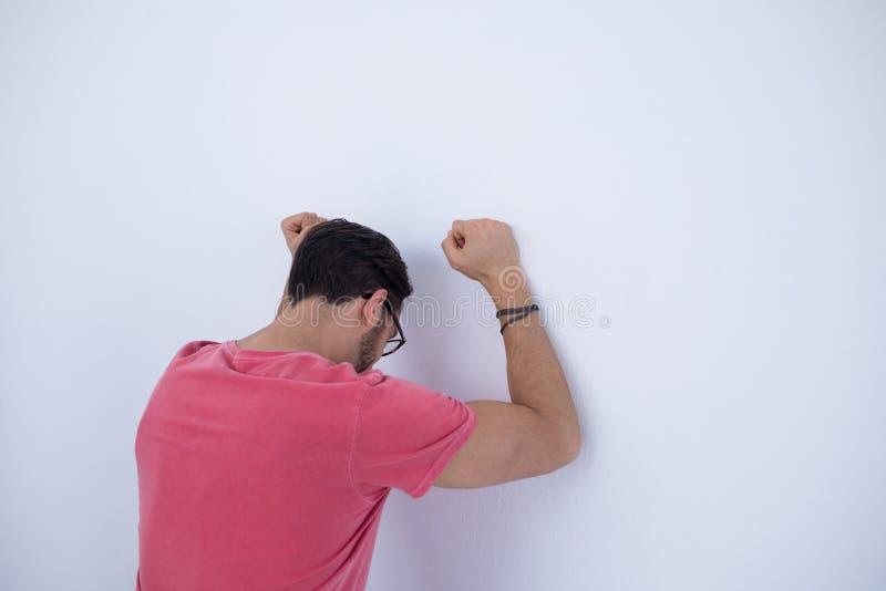 Il dirigente maschio depresso con le armi ha sollevato appoggiarsi la parete immagine stock