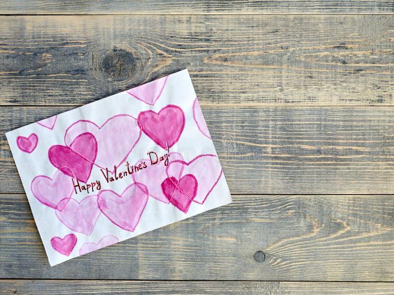 Il disegno dei bambini con i cuori e un'iscrizione per il San Valentino, trovantesi sui bordi strutturati di legno di colore grig immagini stock libere da diritti
