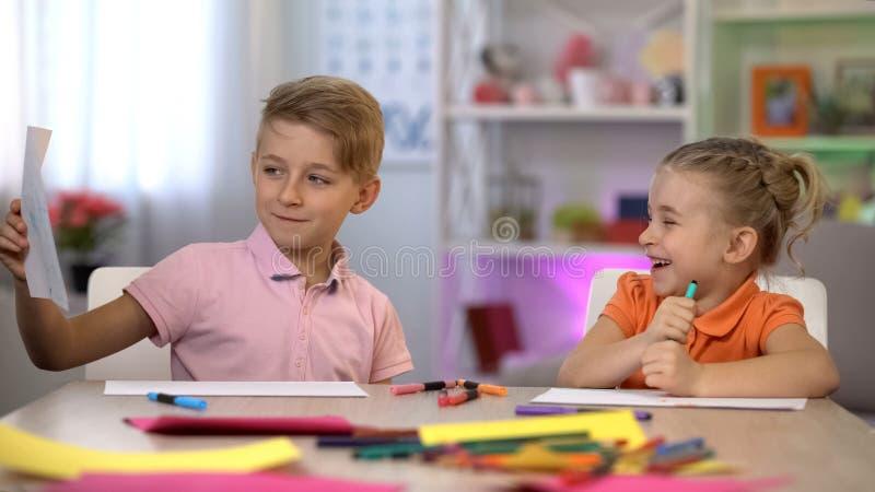 Il disegno di rappresentazione dello scolaro alla sorella, l'amicizia di infanzia, fratelli germani ama, divertimento fotografia stock