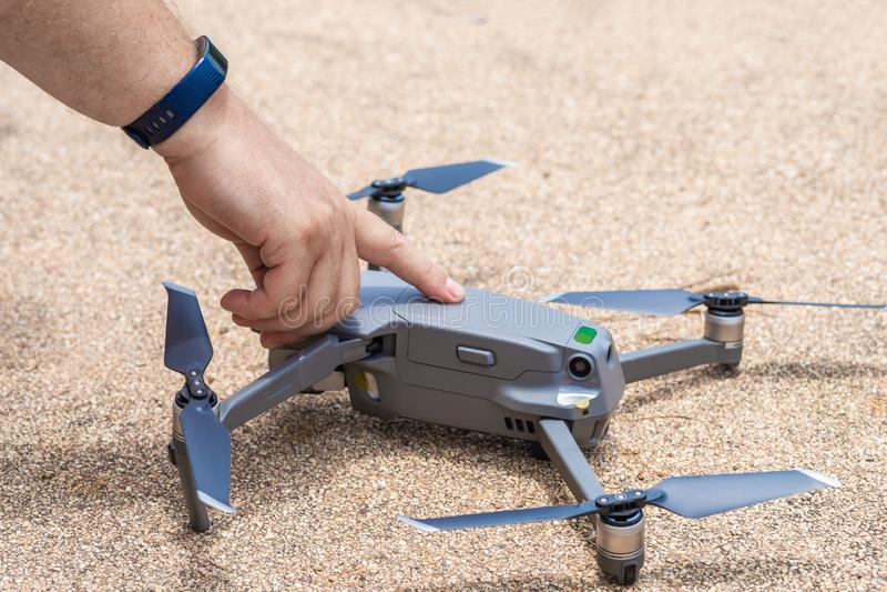 Il dito maschio preme il bottone del lancio del fuco per il volo, con cui potete prendere le foto e la contaminazione del video,  fotografia stock libera da diritti