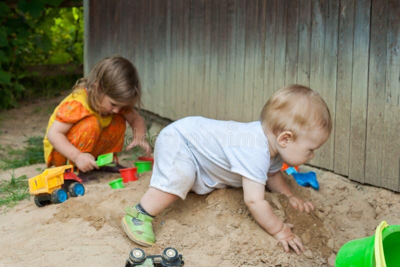 Il divertimento dei bambini dell'estate è un gioco della sabbiera con le pagaie fotografie stock