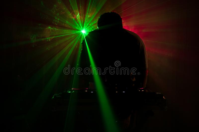 Il DJ che fila, mescolantesi e graffiante in night-club, mani comandi della pista del ritocco del DJ di vari sulla piattaforma de fotografia stock