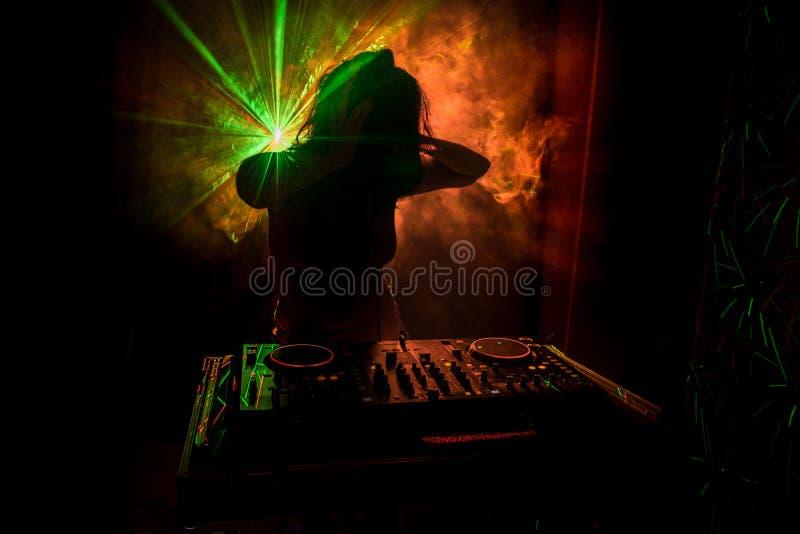 Il DJ che fila, mescolantesi e graffiante in night-club, mani comandi della pista del ritocco del DJ di vari sulla piattaforma de immagini stock