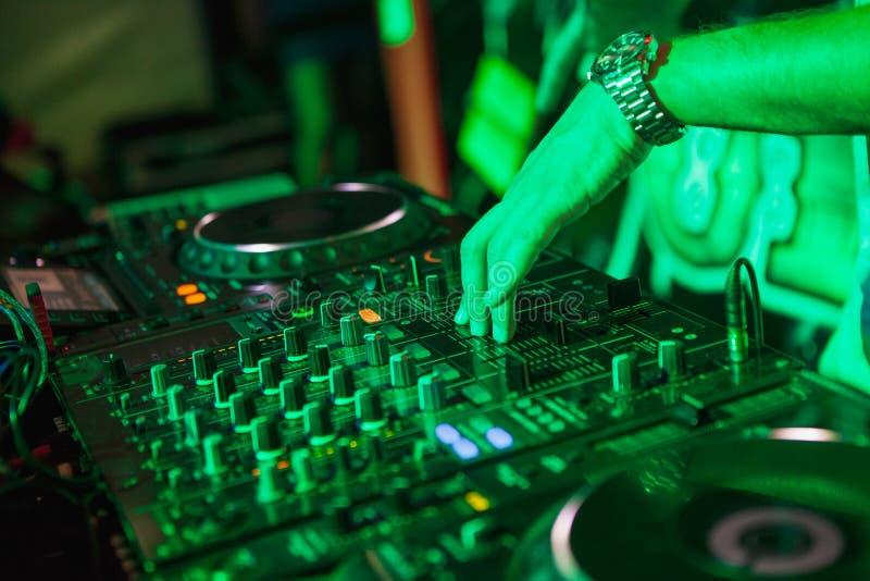 Il DJ che gioca musica al miscelatore su fondo vago variopinto immagine stock libera da diritti