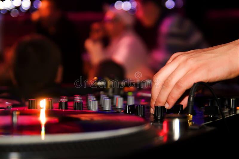 Il DJ che gioca vinile sulla piattaforma girevole nel randello fotografie stock