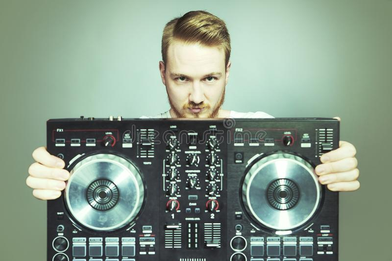 Il DJ con la console per la mescolanza di suoni che posa nello studio immagine stock