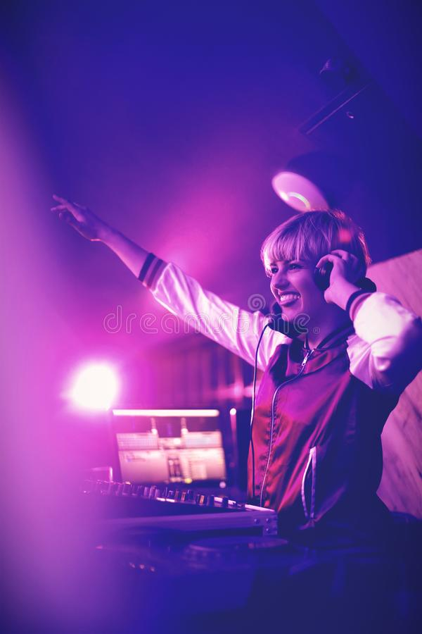 Il DJ femminile che ondeggia la sua mano mentre giocando musica nella barra immagine stock