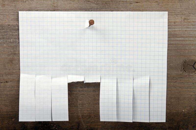 Il documento della pubblicità con il taglio slitta su fondo di legno fotografie stock