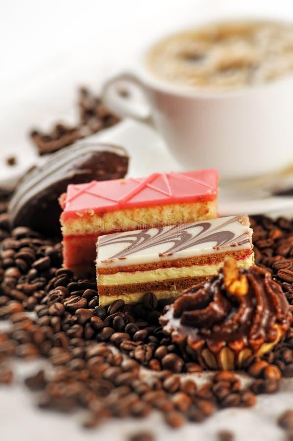 Il dolce agglutina con i chicchi di caffè e la tazza di caffè sulla tavola, la fotografia del prodotto per la pasticceria o la ca immagini stock libere da diritti
